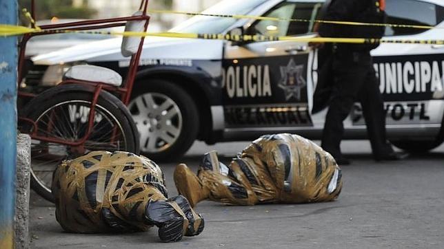 Un agente sale de una zona acotada cerca de dos cadáveres envueltos en plástico en Nezahualcóyotl
