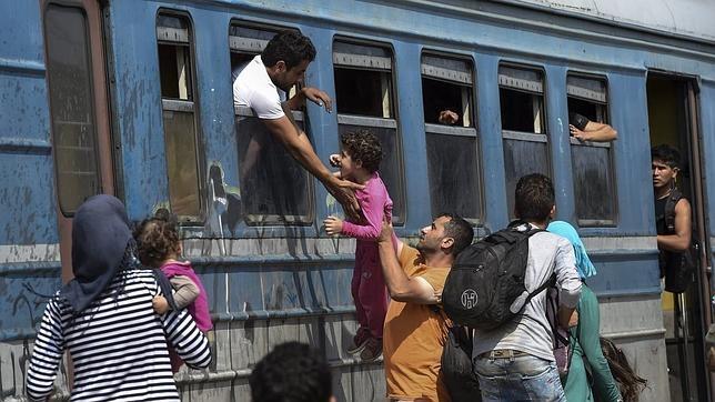 Un grupo de inmigrantes intenta subir a bordo de un tren en la estación de Gevgelija, en Macedonia