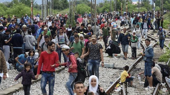 Varios inmigrantes caminan por las vías del tren, en la ciudad de Gevgelija, Macedonia