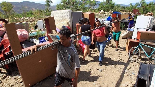 Cientos de colombianos cargan sus pertenencias por el río Táchira desde Venezuela hacia Colombia