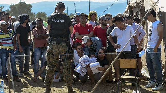 Migrantes esperan a ser inscritos en un nuevo campo de refugiados en la frontera serbia