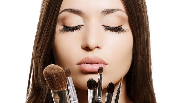 Una mujer muestra varias brochas para maquillar