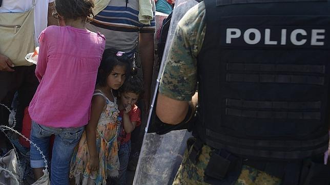 Un grupo de inmigrantes controlados por la Policía macedonia cruzan la frontera entre Macedonia y Grecia