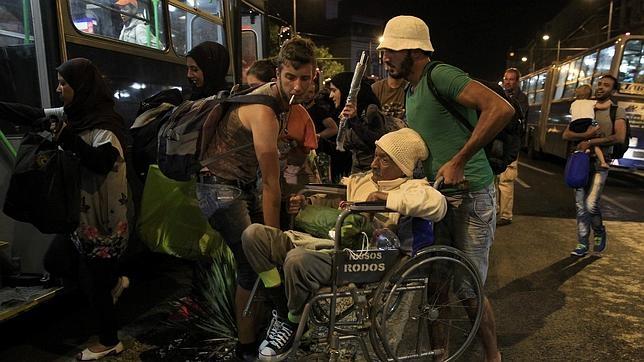 Varios Subir Inmigrantes En Señor Ruedas A De Ayudan Un Silla OvmN8n0w