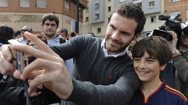 El futbolista Juan Mata se hace un «selfie» con un joven fan en Oviedo