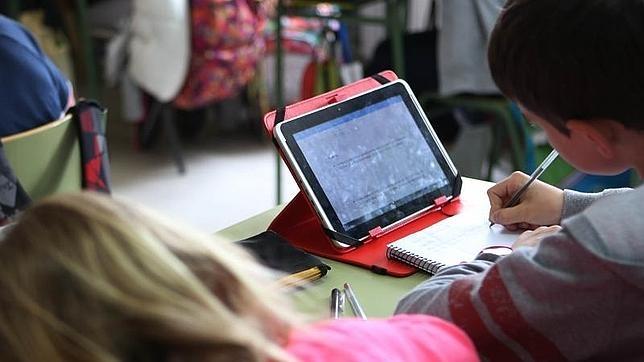 Un grupo de alumnos estudia con una tablet en el aula