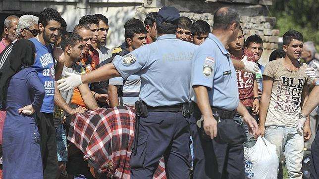 Policías croatas dirigen a varios refugiados a un autobús que les trasladará a un centro de acogida, tras cruzar la frontera con Serbia