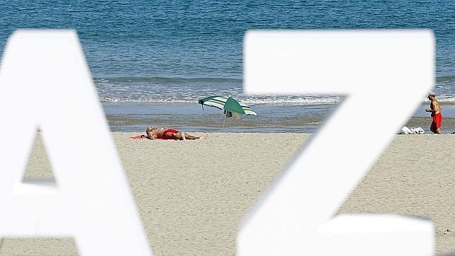 Dos personas disfrutan del sol esta mañana de 21 de septiembre en la playa de La Zurriola de San Sebastián