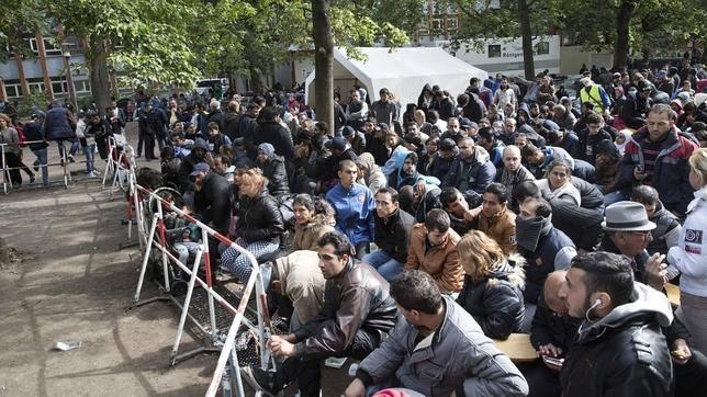 Un grupo de refugiados permanece sentado a la entrada de la Oficina Estatal de Salud y Bienestar de Berlín