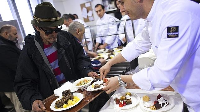 Un hombre recibe alimento en un comedor social madrileño