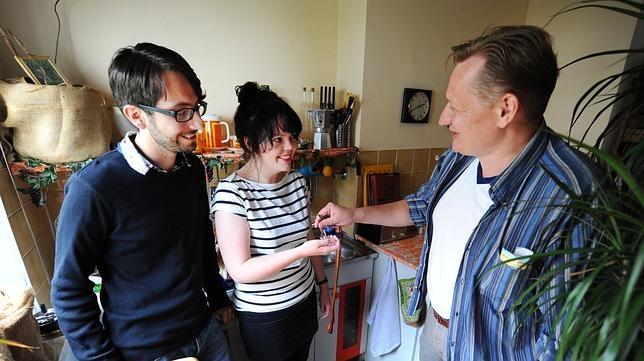 Una persona entrega las llaves de su domicilio a unos viajeros