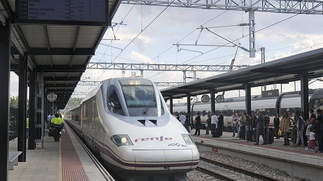 Un grupo de viajeros espera a subir a un tren AVE