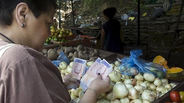 Una venezolana paga su compra con bolívares en un mercado callejero de Caracas