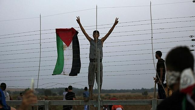 Un jóven palestino cuelga su bandera en la frontera
