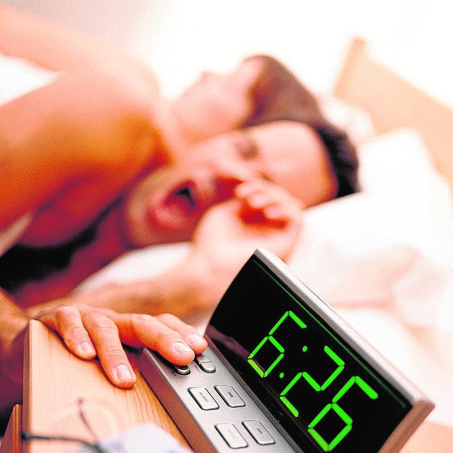 Un hombre apaga su despertador en una imagen de archivo