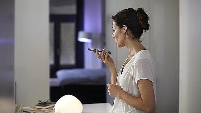 Una mujer gestiona la iluminación del hogar a través de su «smartphone»