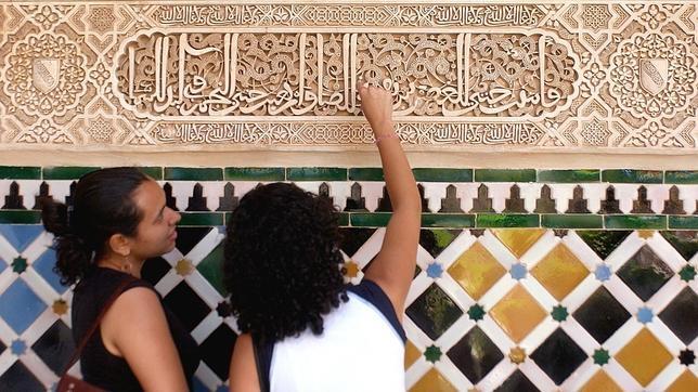 Dos turistas contemplan un fragmento del Corán grabado en uno de los frisos de la Alhambra