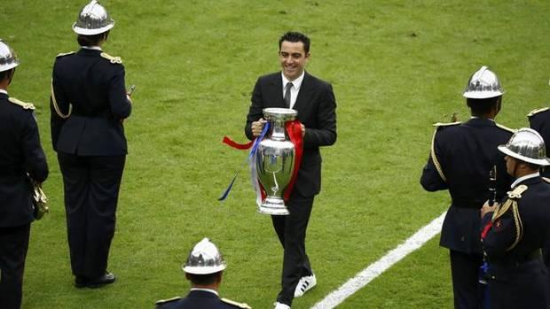 Xavi Hernández entrega el trofeo de ganador de la Eurocopa.