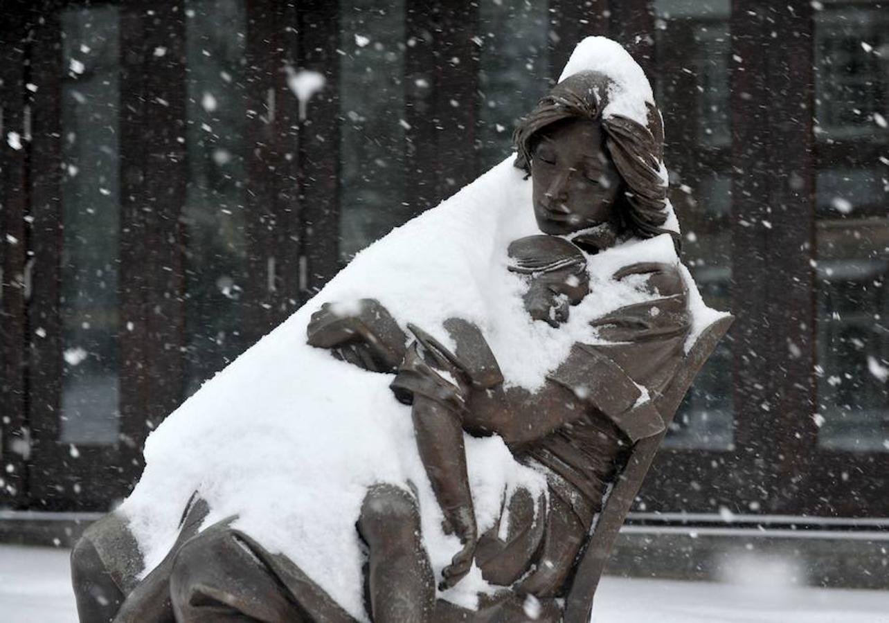 Estatua de una mujer que sostiene a un niño fuera de una galería de arte en Greenwich Avenue en Greenwich, Connecticut