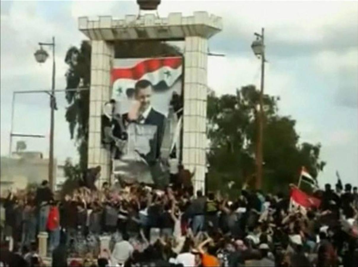 La Guerra de Siria comenzó con la primavera, cuando buena parte del pueblo sirio se levantó contra Bashar al-Assad. En esta imagen amateur del 25 de marzo de 2011, una multitud de sirios desfiguran un cartel del presidente Bashar al-Assad