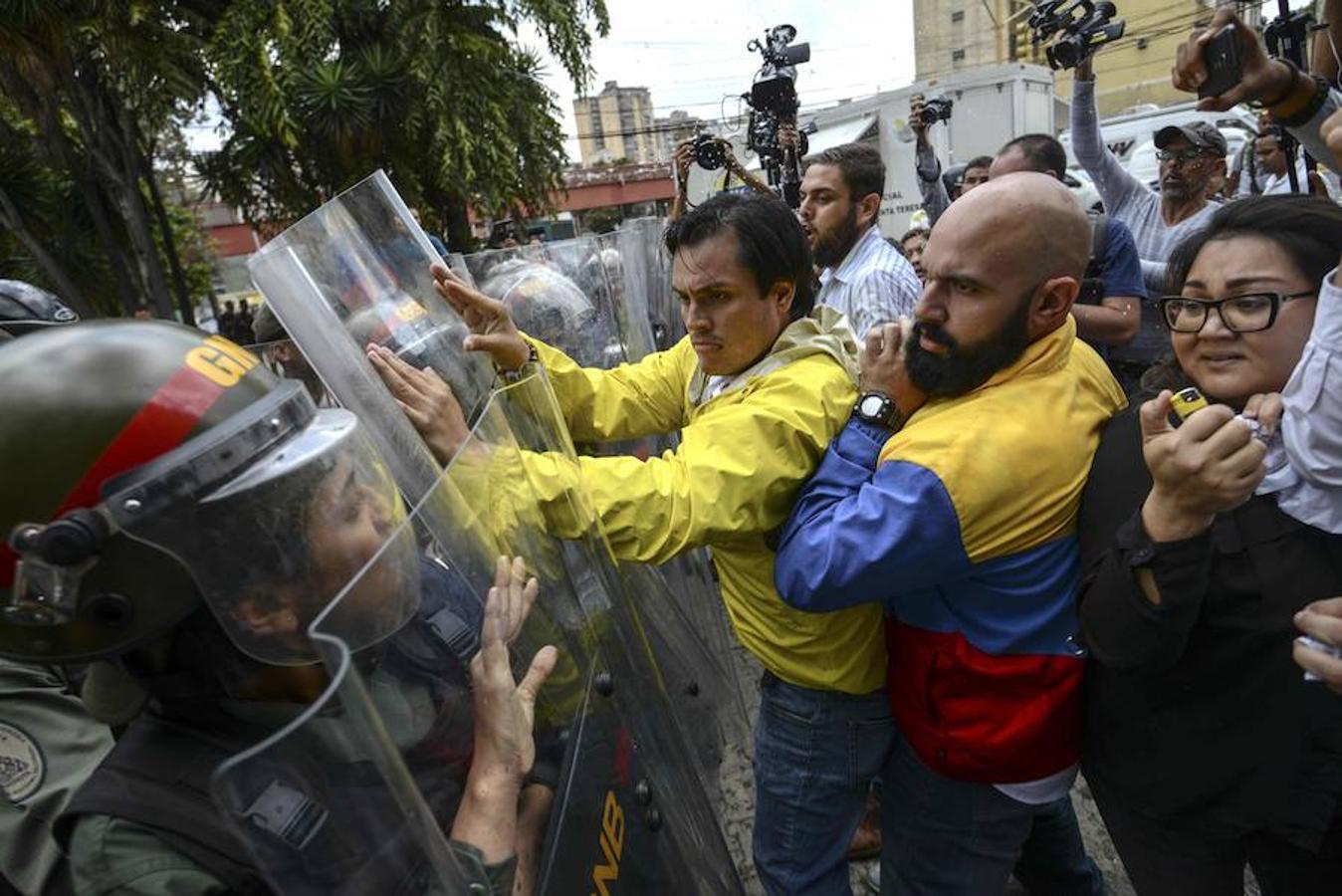 Los diputados de la oposición venezolana Carlos Paparoni y Carlos Bozo empujan los escudos con que se protege la Guardia Nacional en una protesta frente al Tribunal Supremo, en Caracas.