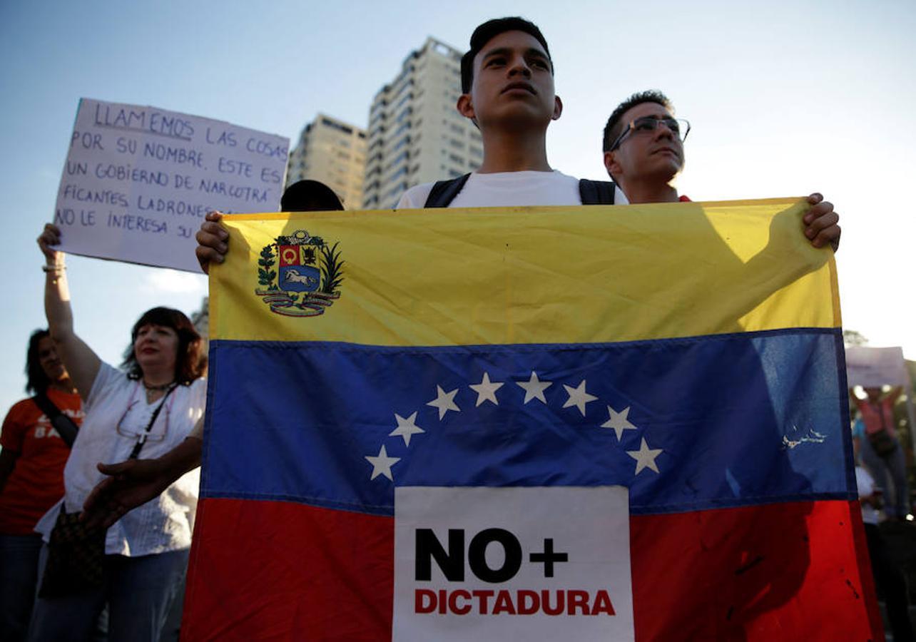 Un estudiante porta una bandera en la que se puede leer «no más dictadura» en una de las protestas organizadas en Caracas