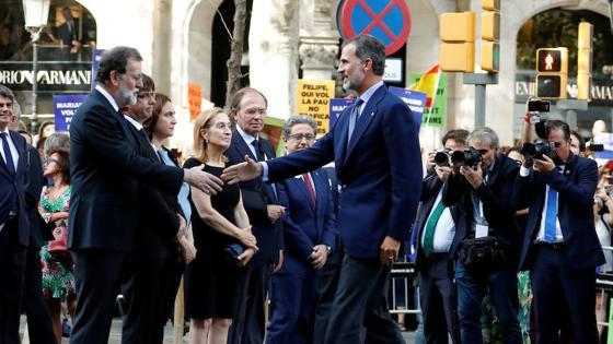 El Rey le da la mano a Mariano Rajoy durante la manifestación