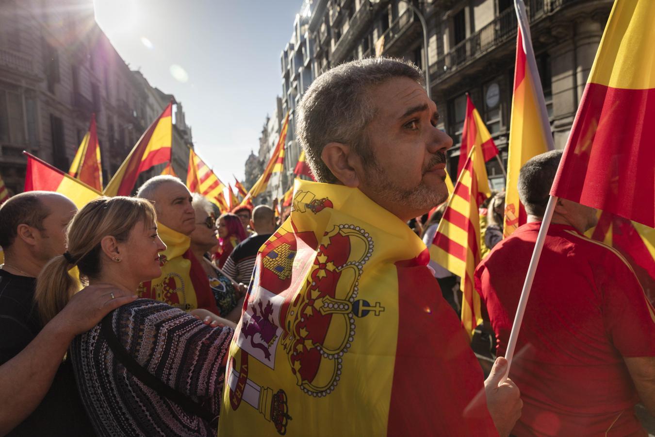 Entre multitud de banderas españolas, «senyeres» y europeas, los manifestantes continúan gritando consignas como «Puigdemont a prisión», «Yo soy español» o «Viva España, viva Cataluña y viva la Guardia Civil»