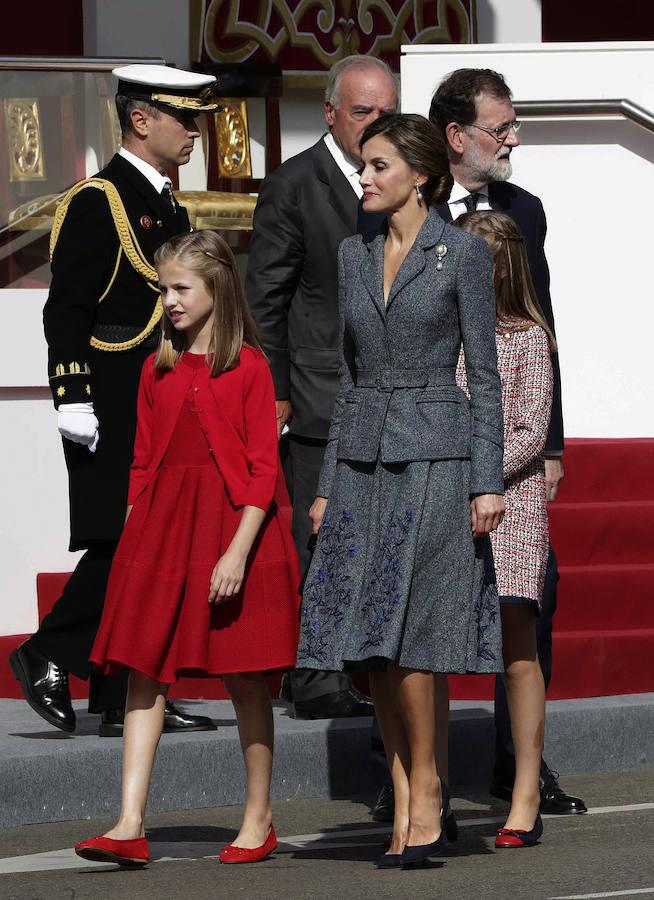 Este 12 de octubre, Doña Letizia ha vuelto a apostar por su diseñador fetiche, Felipe Varela. La Reina ha optado este año por un traje de chaqueta gris azulado con un bordado en la falda y un broche con perla en la solapa, además del cabello recogido