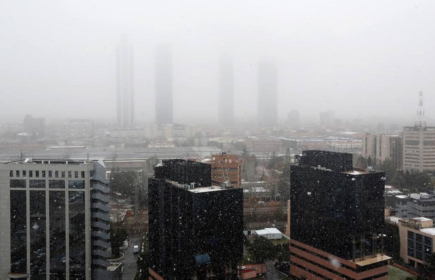 La nieve en Madrid ha empezado tímida y cayendo sobre mojado, pero a media mañana ha conseguido cuajar sobre vehículos y jardines. Vista del distrito financiero Cuatro Torres Business Area