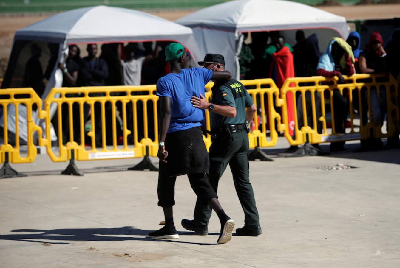 Un inmigrante rodea con el brazo a un guardia civil que cuida y vigila a las personas que llegan en patera a las costas de Cádiz y son trasladadas al pabellón «Antonio Gavira», en el municipio Los Barrios, cerca de Algeciras.