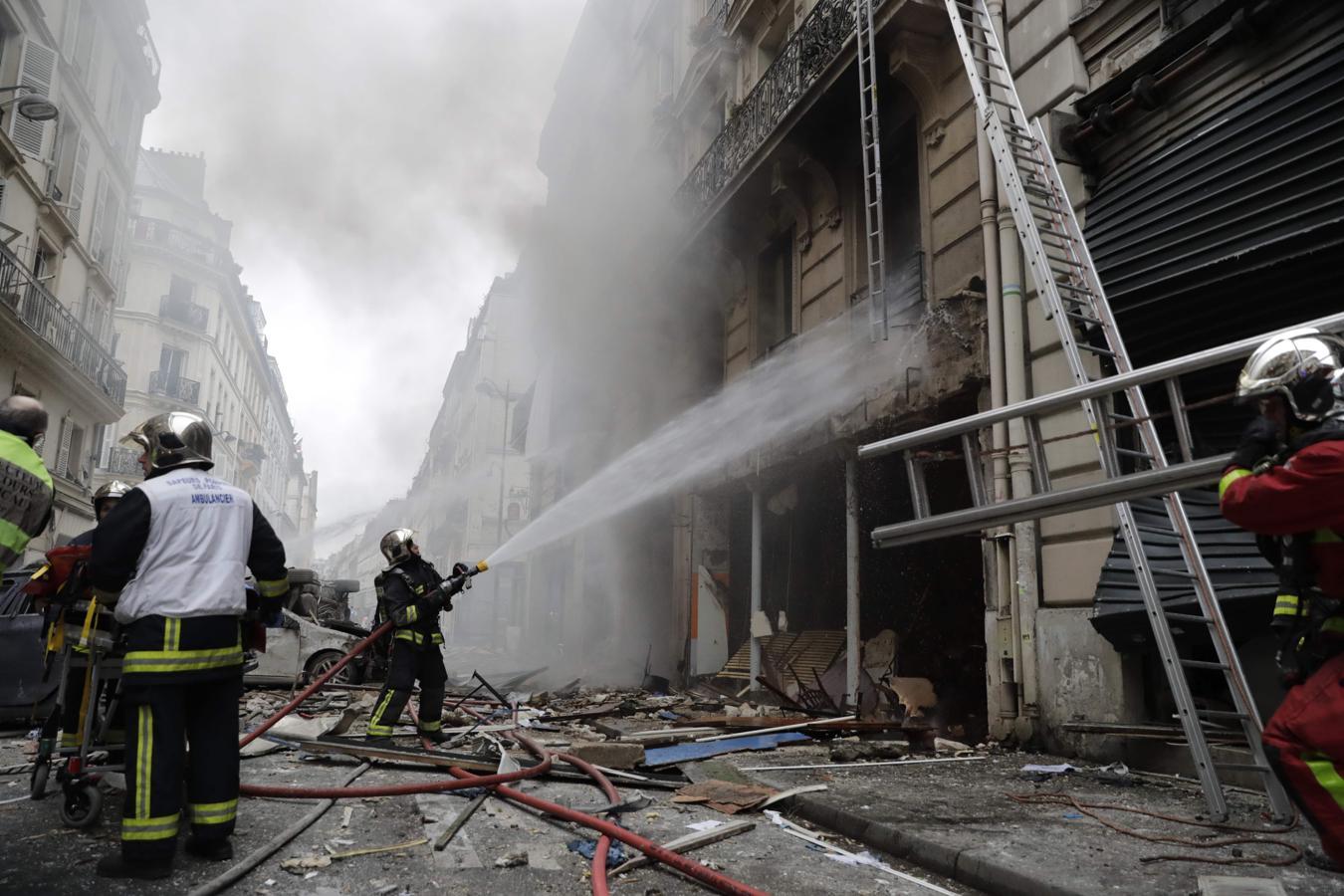 Los bomberos trabajan en la extinción del fuego de la panadería quemada en París