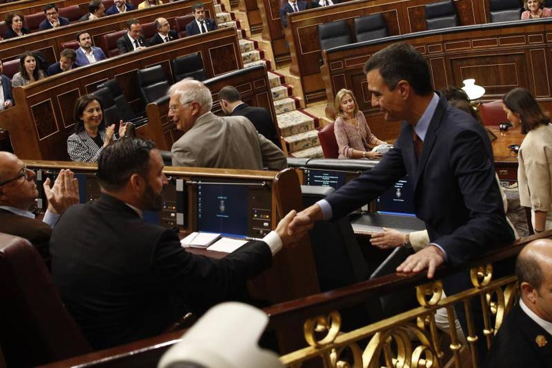 Pedro Sánchez saluda a Santiago Abascal, que ocupa un escaño en la bancada socialista