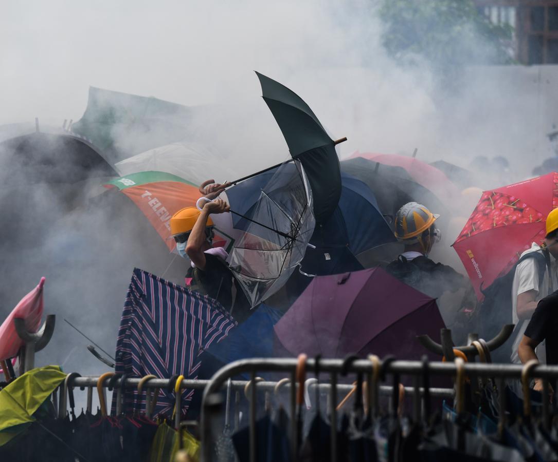 Un grupo de manifestantes responden golpeando con paraguas a los policías tras el lanzamiento de gas pimienta.