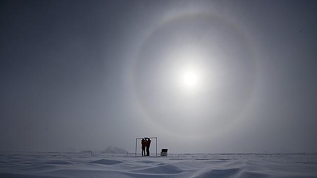 Imagen tomada el 18 de noviembre de 2015 que muestra a dos científicos midiendo la radiación solar y su albedo en el campamento Glaciar Union