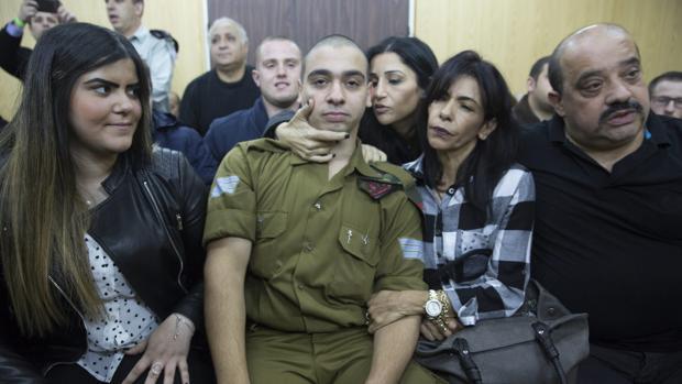 El soldado israelí Elor Azaria (c) espera junto a su familia a la lectura de la sentecia durante su juicio por disparar y matar a un atacante palestino reducido e inmovilizado