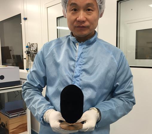 Un especialista sostiene un busto rociado con «Vantablack»