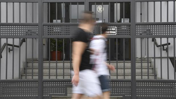 Dos jóvenes pasan por delante del domicilio de Segovia donde la Policía detuvo en el día de ayer a Pedro Luis Gallego