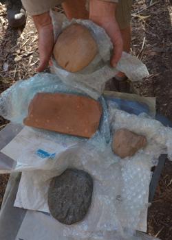 Tres hachas de diferentes capas del sitio y una piedra de afilar rectangular del nivel de 65.000 años