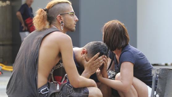 Varios jóvenes permanecen junto a los restos de un vehículo, en el lugar del atropello masivo de una furgoneta que ha arrollado esta tarde a varias personas que paseaban por las Ramblas de Barcelona.