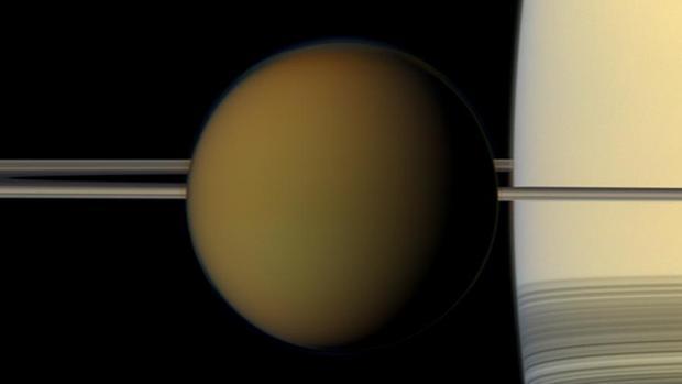 Titán en frente de los anillos de Saturno, el planeta que se ve a la derecha