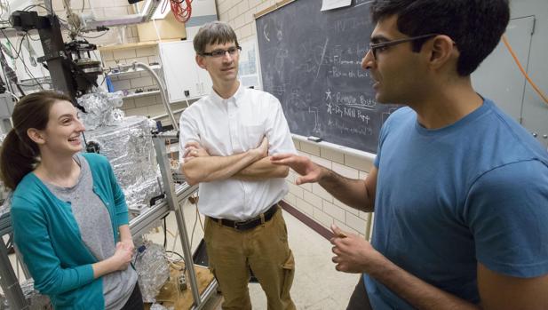 El profesor de Física Peter Abbamonte (centro) trabaja con estudiantes graduados en su laboratorio en la Universidad de Illinois