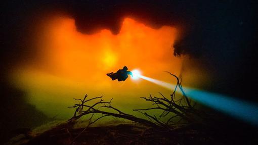 Un buceador se adentra en un cenote iluminado por el Sol