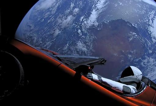 Un automóvil Tesla Roadster rojo cereza flota en el espacio después de que fue transportado allí por el Falcon Heavy de SpaceX