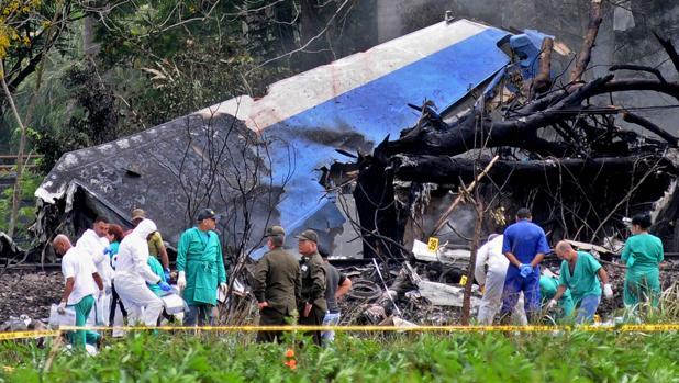 Policías y militares trabajan entre los restos del avión Boeing-737 estrellado