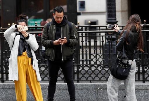 Unos jóvenes miran su teléfono móvil. Internet está cambiando el modo de buscar pareja, según expertos