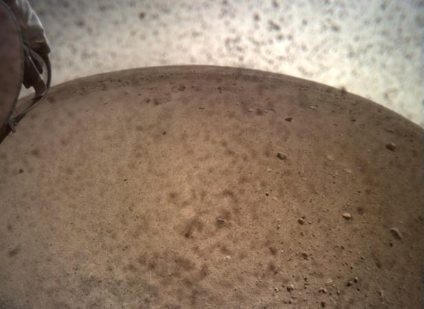 La nave espacial InSight abrió la tapa de la lente de su Cámara de Contexto de Instrumentos (ICC) el 30 de noviembre y capturó esta vista de Marte. Ubicada debajo de la cubierta del módulo de aterrizaje, la ICC tiene una vista de ojo de pez, creando un horizonte curvo.