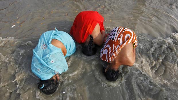 Tres peregrinas hindúes se bañan en las contaminadas aguas del río Ganges