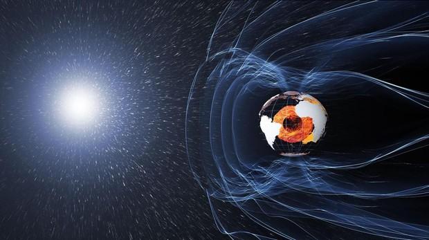 El campo magnético de la Tierra es generado por el núcleo (en naranja). Protege la atmósfera frente al viento solar y la superficie de los rayos cósmicos