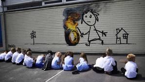 Los alumnos de la escuela observan el mural, obra de Banksy